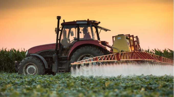Tractor rociando plaguicidas en campo agrícola.