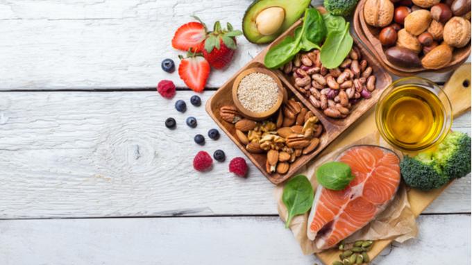 Mesa de madera con alimentos saludables: frutas, semillas, vegetales.