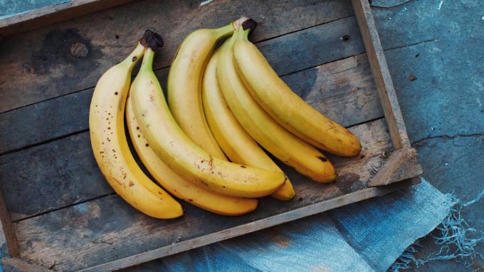Bandeja de madera sobre superficia azul. Manojo de bananos.
