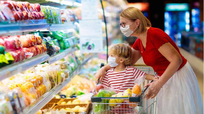 Mujer y niño de compras en supermercado. Contexto COVID.