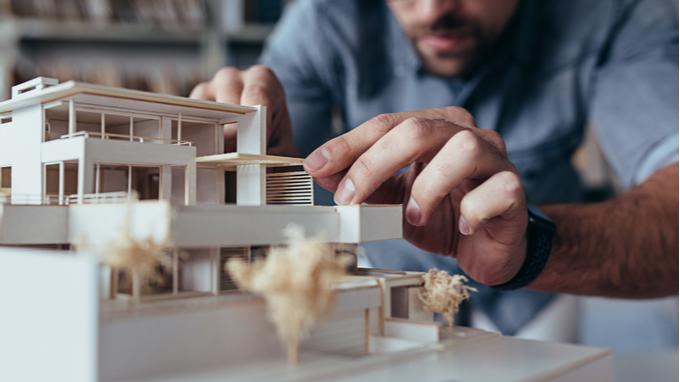 Arquitecto finalizando una maqueta de construcción sostenible.