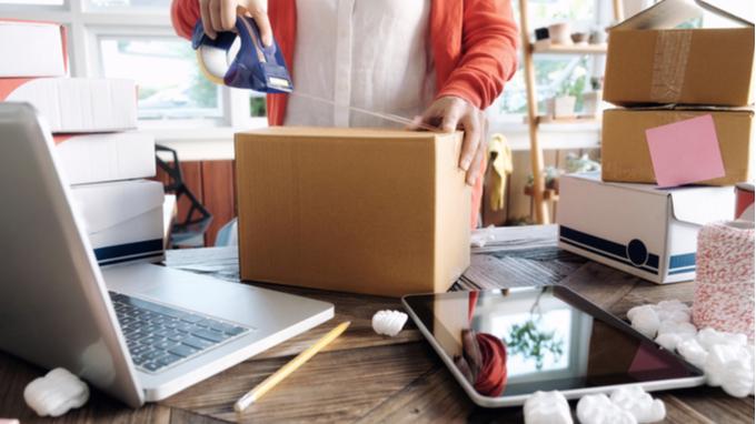 Mujer atendiendo negocio de venta en línea. Cajas y computadora.