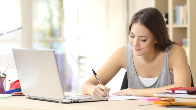 Mujer joven estudiando desde casa.