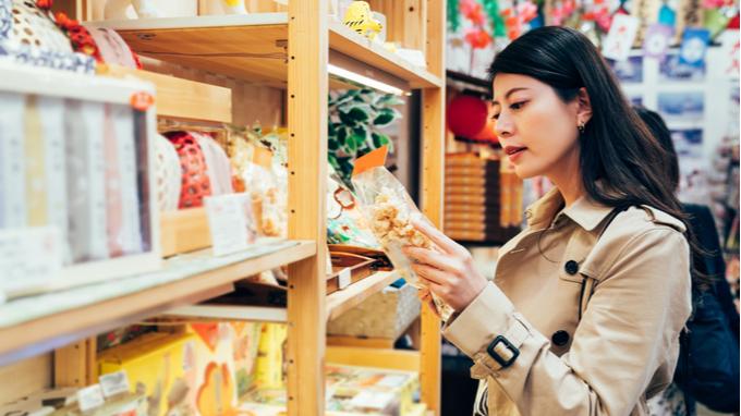 Mujer en comercio revisando etiquetado de producto alimenticio.