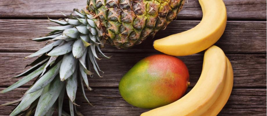 Piña, banano y mango sobre mesa de madera.