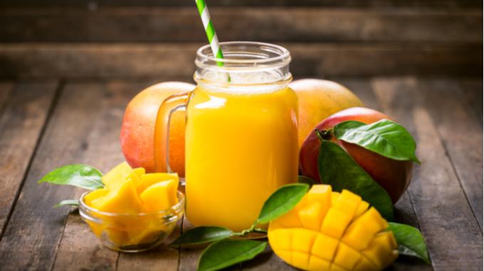 Jugo de mango y platos con trozos de mango fresco.