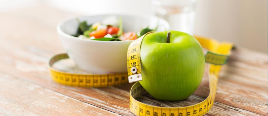Plato de ensalda, manzana verde y cinta de medición.