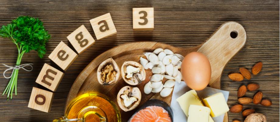 Tabla de madera con alimentos que contienen omega 3: huevo, pescado, aceite, otros.