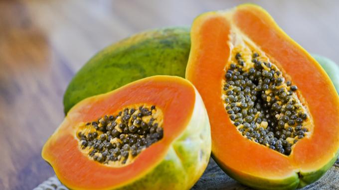 Papaya rebanada a la mitad sobre base de madera.
