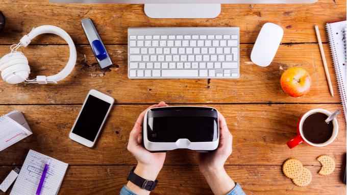 Escritorio de oficina con computadora, celular y lentes de realidad virtual