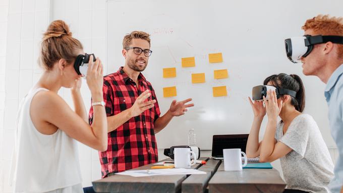 Grupo de jóvenes emprendedores con lentes de realidad virtual.