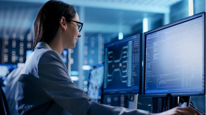 Mujer de lentes frente a computadora. Tecnologías de la información y comunicación.