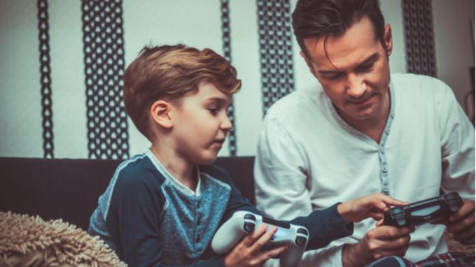 Niño y adulto jugando videojuegos.